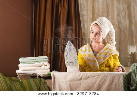 Little Funny Housewife With Iron. Iron In The Hand Of The Girl On The Ironing Board Irons And Steams