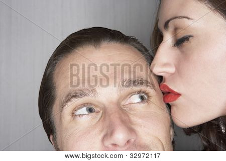 Woman kissing man on temple