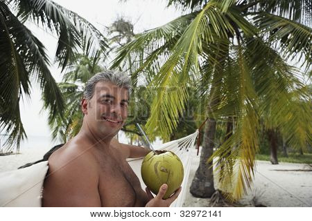 South American man drinking from coconut