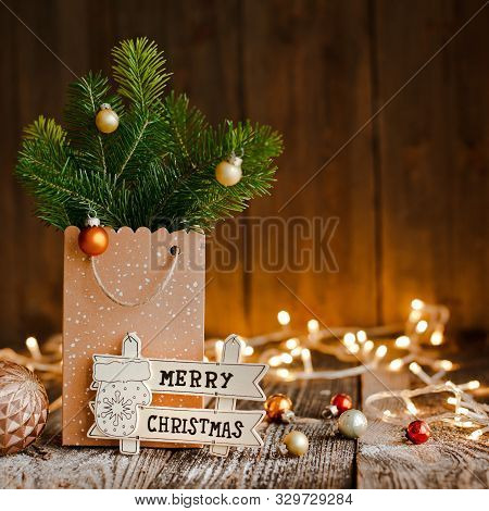 Christmas Composition. Paper Bag With And Bumps Fir Branches On Brown Wooden Background And Bokeh Li