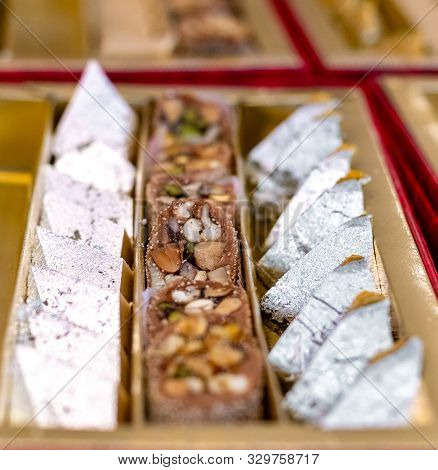A mixture of various Indian sweets packed in a box. Peda, laddu, mithai, diwali sweets poster
