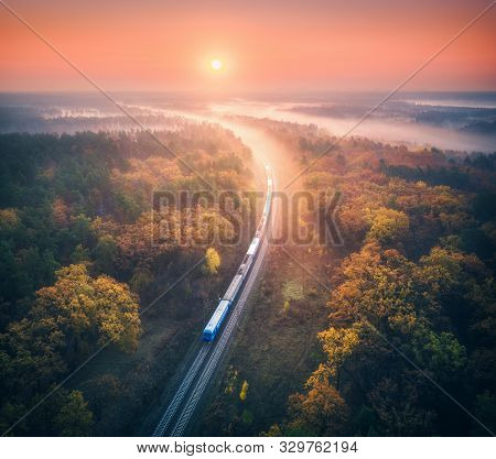 Train In Beautiful Forest In Fog At Sunrise In Autumn. Aerial View Of Commuter Train In Fall. Colorf