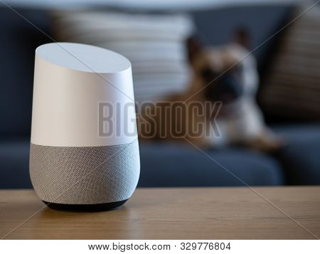Smart Home Voice Activated Speaker In Lounge With Pet Dog In Background