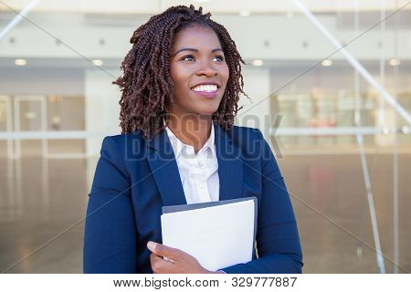 Happy Excited Professional With Documents Walking Outside. Young Black Business Woman Standing At Gl