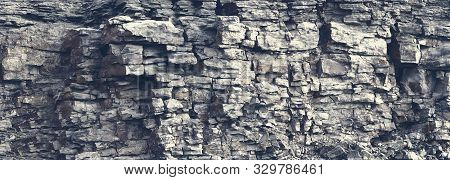 Dangerous Vertical Wall With Protruding Crumbling Layered Wild Stone Blocks. Rock Cliff Face Backgro