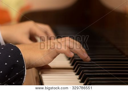 Close Up Side View Of Child Hands Playing The Piano. Selective Focus. Boy Fingers And Beautiful Blac
