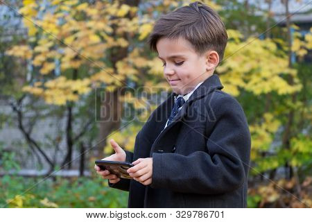 A Smiling Happy Schoolboy Is Standing In The Street In A Beautiful Business Suit Holding A Smartphon