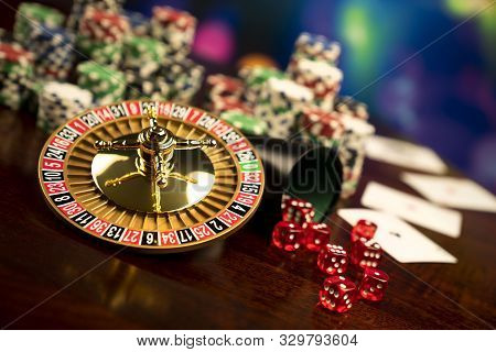 Casino Theme.  Gambling Games. Roulette, Dice, Cards And Poker Chips On A Colorful Bokeh Background.