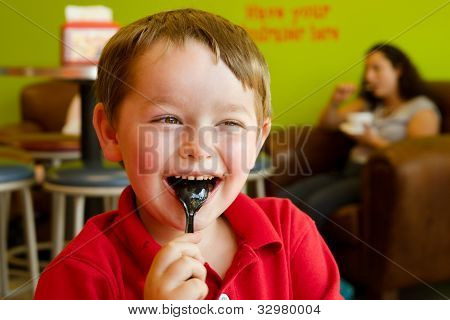 Young boy eating chocolate frozen yogurt at frozen yogurt or ice cream shop