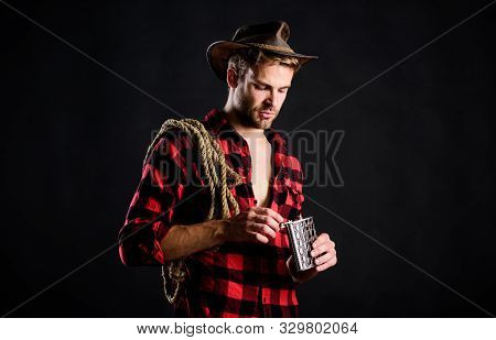 Cowboy Drink. Man Checkered Shirt On Ranch. Wild West Rodeo. Man In Hat Black Background. Cowboy Wit