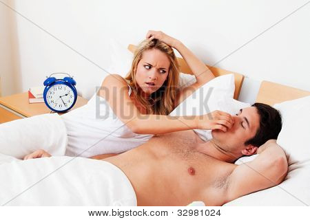 couple in scvhlafzimmer. husband snores loud and unpleasant.