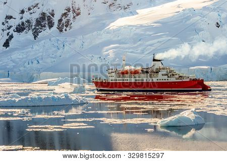 Red Cruise Steamboat Drifting Among The Icebergs With Huge Rock And Glacier In Background, Neco Bay,