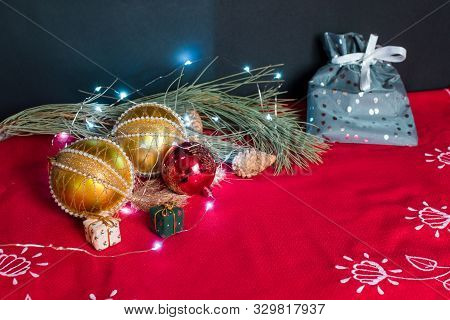 Still Life Of Christmas Accessories On Black Background And Red Tablecloth