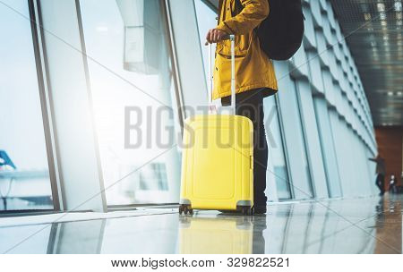 Traveler In Bright Jacket With Yellow Suitcase Backpack At Airport On Background Large Window Blue S