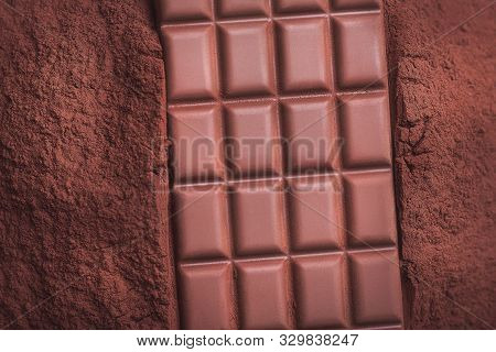 Chocolate Background With A Milk Chocolate Bar On Pile Of Cacao Powder. Chocolate Close-up. Chocolat