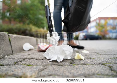 Woman Collecting Trash Outdoors Using Litter Picker
