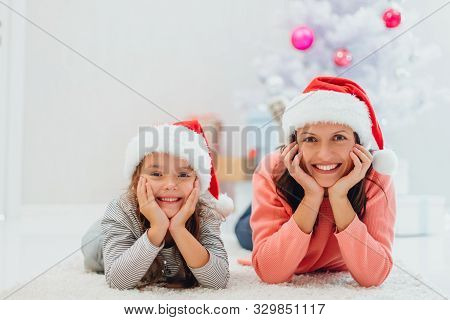 Closeup Photo Of Young Mother And Daughter Lying On The Carpet Near Fir-tree, Enjoying Time Together