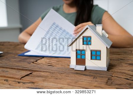 Cropped Image Of Businesswoman Doing Calculation By Model House On Table