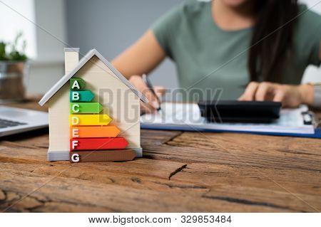 House With Energy Efficiency Rate In Front Of Businessperson Working In Office While Using Calculato