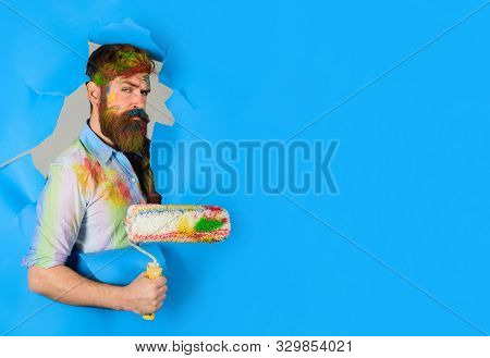 Painter. Painter With Painting Roller Through Hole In Paper. Handsome Bearded Worker With Paint Roll