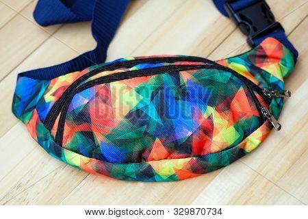 bright waist bag close-up. on the wooden floor lies a waist bag (bum bag) top view. accessories for tourism. poster