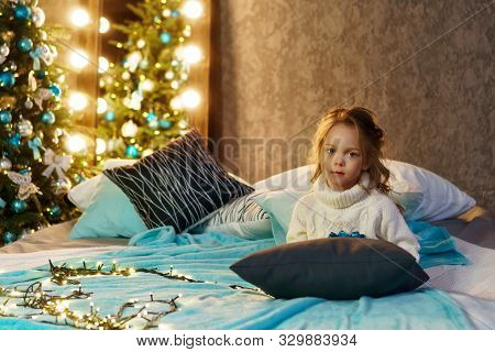 Cute Little Girl In A Warm White Sweater Sitting On The Cozy Bed Near Christmas Tree In Evening At H
