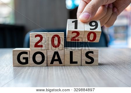 Business Man Hand Holding Wooden Cube With Flip Over Block 2019 To 2020 Goals Word On Table Backgrou