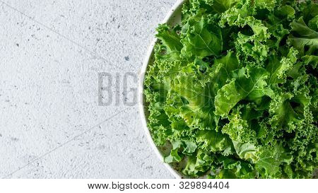 Kale Close Up. Green Vegetable Leaves, Top View In White Craft Bowl Over Gray Cement Background. Hea