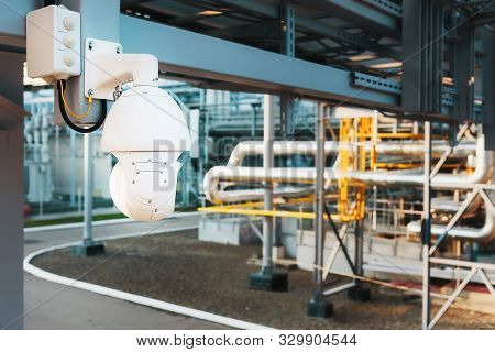 Security Camera, White Round Wide Angle Operated. Security System At A Factory In An Industrial Zone