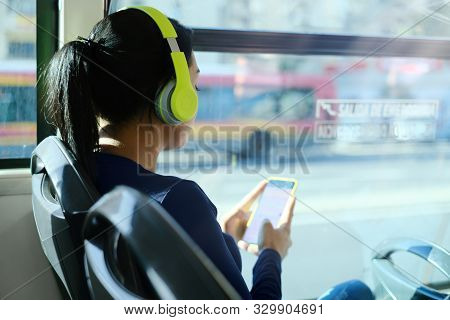 Woman With Headphones Listening To Music Commuting By Bus