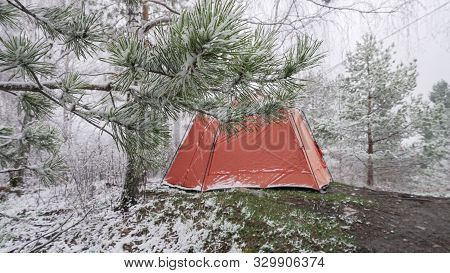 A Red Tent In The Winter Forest In The Background Behind The Trees. Focus On Tree Branches And Snow