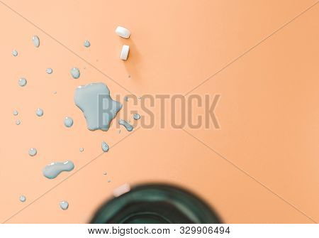 Overhead View Of Medication Drug Tablets On Orange Surface With Water Splash And Copy Space