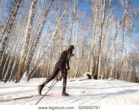 Cross-country Skiing Training In The Winter Forest. Aerobic Load For The Cardiovascular System.