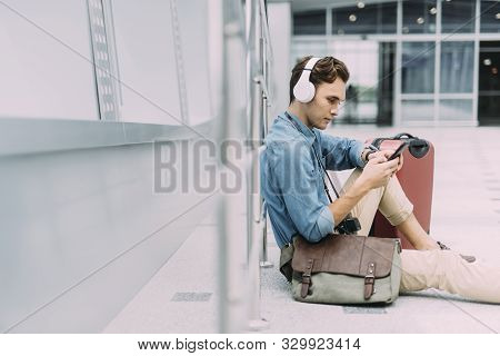 Male Wasting Time With Gadgets At Airport Stock Photo