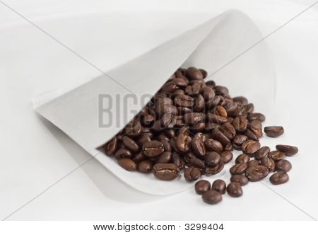 Coffee Beans Spill From Paper Cone Filter