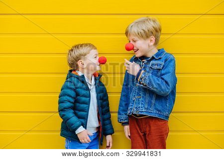 Red Nose Day Concept. Happy Little Brothers Looks At Each Other Wearing Red Clown Noses Having Fun T