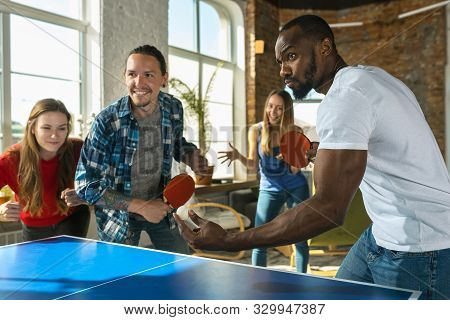 Young People Playing Table Tennis In Workplace, Having Fun. Friends In Casual Clothes Play Ping Pong