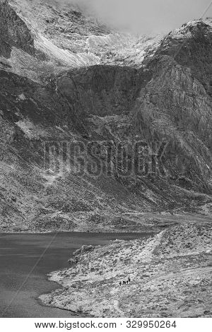 Stunning Dramatic Winter Landscape Image Of Llyn Idwal And Snowcapped Glyders Mountain Range In Snow