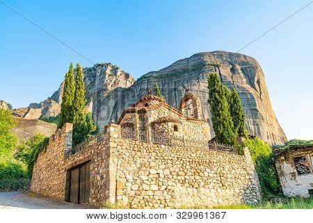 Large Imposing Rocks Rise Behind Quaint Greek Orthodox Stone Church In Town Of Kastraki, Meteora Gre