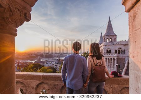 Young Couple Enjoy The View From The Point From Fisherman Bastion In Budapest During Sunrise.