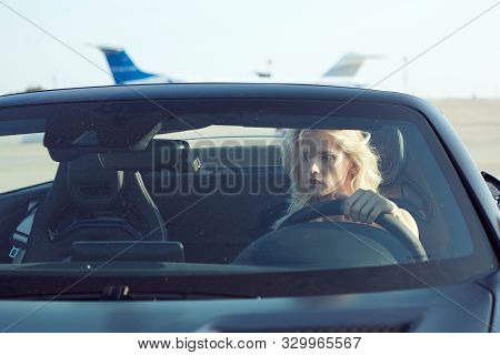 One Glamorous Blonde Woman Sit In Cabriolet Car, Glamour Girl Inside Cabrio Auto On The Runway. No R