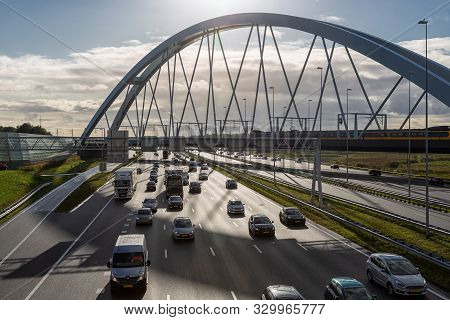 Muiden, The Netherlands - October 03, 2019: Rush Hour At Dutch Motorway A1 Near Amsterdam With Railw