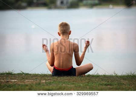 A Young Boy Practices Focus On Water By Practicing Yoga