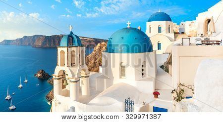 Local Church With Blue Cupola In Oia Village, Santorini Island, Greece. Panoramic Image With Oia Sky