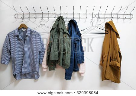 A Shirt, Jackets And A Hanger Hang On A Metal Wall Hanger. Womens Clothes Hanging On A Wall Hanger.