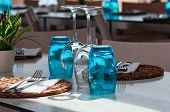 Table setup in restaurant on sunny day outdoor, served for lunch, blue glasses, wicker plates, cutlery. Simple, authentic decor. Beautiful summer holiday concept. Romantic time at resort. Selective focus poster