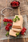 foie gras and red currant on wood background poster