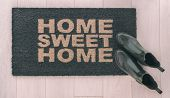 Home Sweet Home doormat entrance mat at front door of new condo in urban city living with stylish womens rain boots of homeowner resting on top. poster