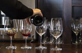 Woman Pouring Red Wine Into Four Crystal Glasses For A Wine Tasting