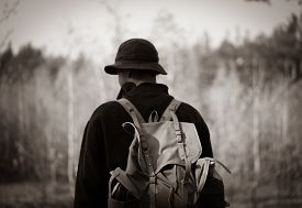 Young Guy With A Vintage Backpack In The Forest. Black And White.